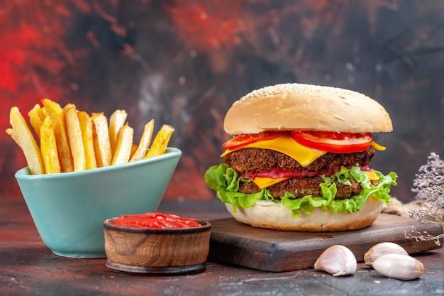 Vorderansicht leckeren fleischburger mit pommes frites auf dunklem schreibtisch
