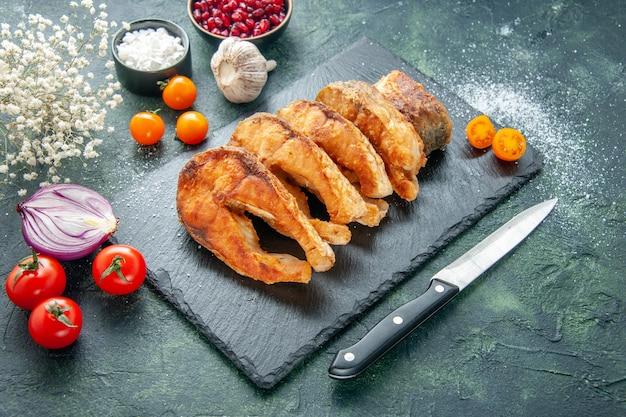 Vorderansicht leckeren gebratenen fisch mit tomaten auf dunkelblauer oberfläche mahlzeit pfeffer kochgericht braten meeresfrüchte meeresfleisch lebensmittel salat