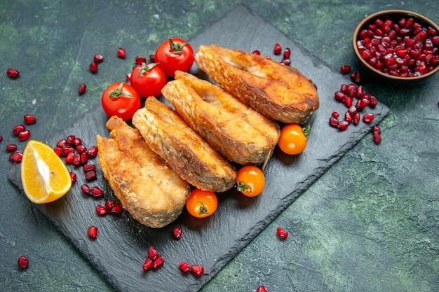 Vorderansicht leckeren gebratenen fisch mit tomaten auf dunkler oberfläche mahlzeit meeresfrüchtesalat meeresfrüchte kochen braten gericht fleisch