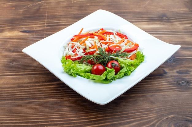Vorderansicht leckeren gemüsesalat mit grünem salat und kohlinnenplatte auf brauner oberfläche