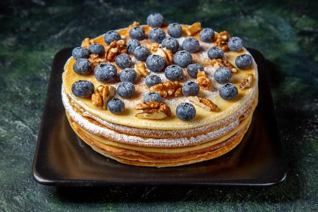 Vorderansicht leckeren honigkuchen mit blaubeeren und walnüssen innerhalb platte dunkle oberfläche