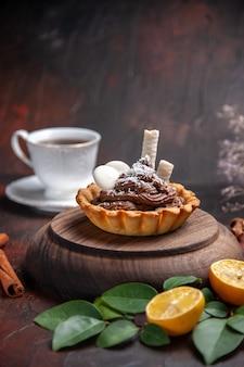 Vorderansicht leckerer cremiger kuchen auf dunklem tischdessert süßer kekskuchen