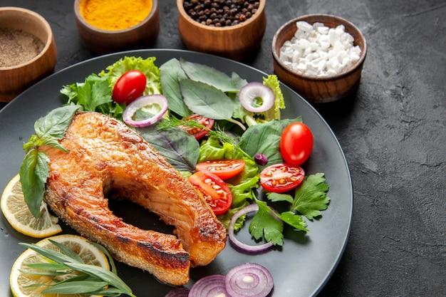 Vorderansicht leckerer gekochter fisch mit frischem gemüse und gewürzen auf dunklem hintergrund farbe lebensmittel fleisch meeresfrüchte gericht foto