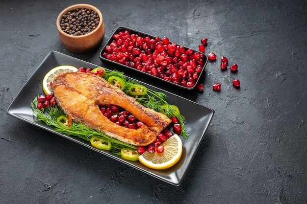 Vorderansicht leckerer gekochter fisch mit granatäpfeln und zitronenscheiben in der pfanne auf dunkelgrauem hintergrund gericht farbe lebensmittel foto fleisch gesundheit meeresfrüchte