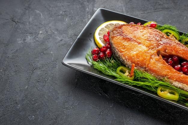 Vorderansicht leckerer gekochter fisch mit grüns und zitronenscheiben in der pfanne auf dunklem hintergrund farbe obst meeresfrüchte essen gericht foto fleisch