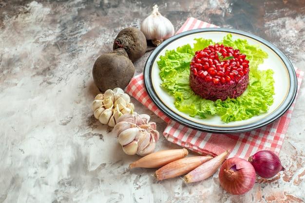 Vorderansicht leckerer granatapfelsalat auf grünem salat mit frischem gemüse auf leichtem fotoessen