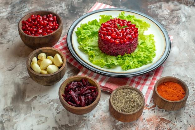Vorderansicht leckerer granatapfelsalat auf grünem salat mit gewürzen auf hellem fotoessen mahlzeit farbe gesunde ernährung lecker