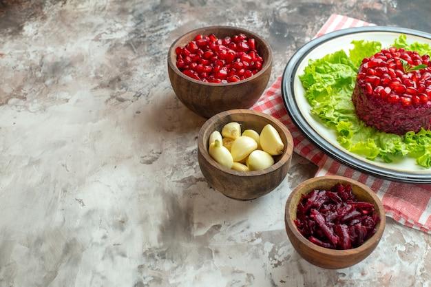 Vorderansicht leckerer granatapfelsalat auf grünem salat mit gewürzen auf hellem fotoessen mahlzeit farbe gesundheit leckerer freiraum free