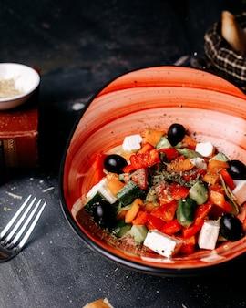Vorderansicht leckerer griechenland-salat mit gemüse und weißem käse in schwarzen teller auf dem dunklen schreibtisch geschnitten