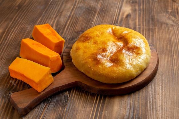 Vorderansicht leckerer kürbiskuchen mit geschnittenem kürbis auf braunem hölzernem schreibtischkuchenkuchen backofen