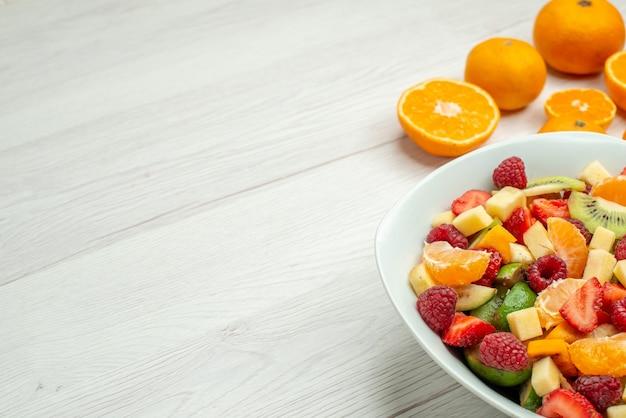 Vorderansicht leckerer obstsalat mit frischen mandarinen auf weißem mellow beere foto fruchtige baumreife gesundheit