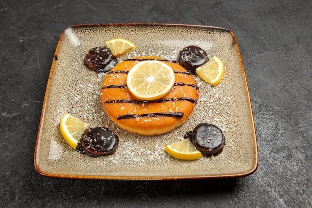 Vorderansicht leckerer süßer kuchen mit schokoladensauce und zitronenscheiben auf grauem hintergrund kuchenkuchen keks teig süßer keks
