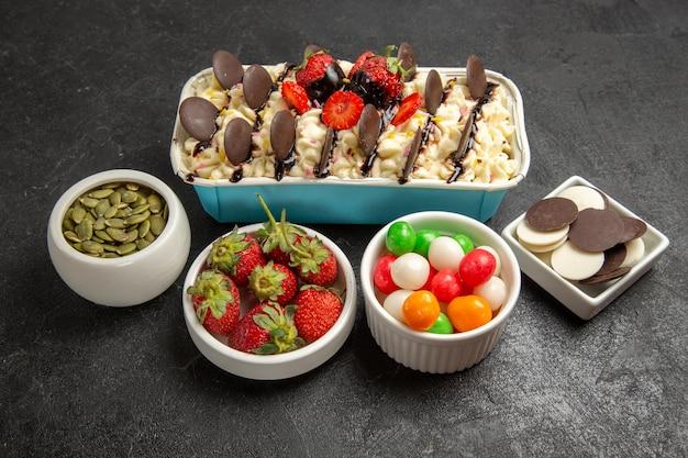 Vorderansicht leckeres dessert mit keksen und bonbons auf dunklem hintergrund nusskeks süßer fruchtplätzchenzucker