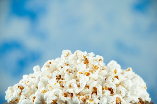Vorderansicht leckeres frisches popcorn im teller auf hellblauem hintergrund