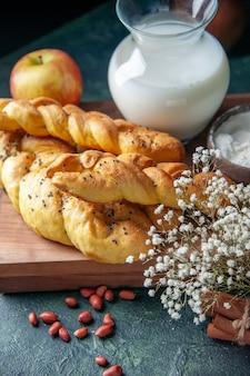Vorderansicht leckeres gebäck mit äpfeln und milch auf dunklem tischkuchen kuchen hotcake süßes brötchen dessert teig zucker