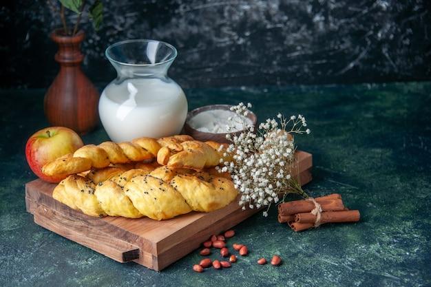 Vorderansicht leckeres gebäck mit mehl und milch auf dunklem tischkuchen kuchen hotcake süßes brötchen dessert teig zucker