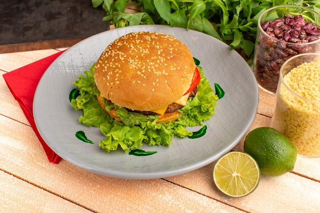 Vorderansicht leckeres hühnchensandwich mit grünem salat und gemüse innerhalb platte auf dem hölzernen sahne-schreibtisch.