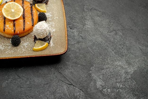 Vorderansicht leckeres kuchendessert mit zitronenscheiben und kokosbonbons auf dunklem hintergrund kuchendesserttee süße kuchenbonbons