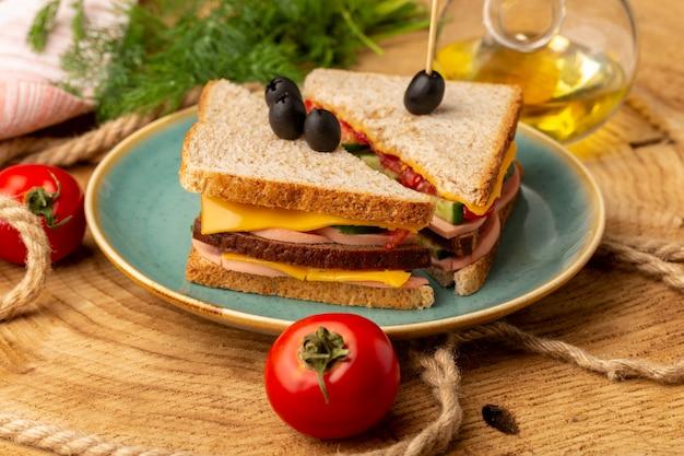 Vorderansicht leckeres sandwich mit olivenschinken tomaten in platte zusammen mit öl tomaten auf holz