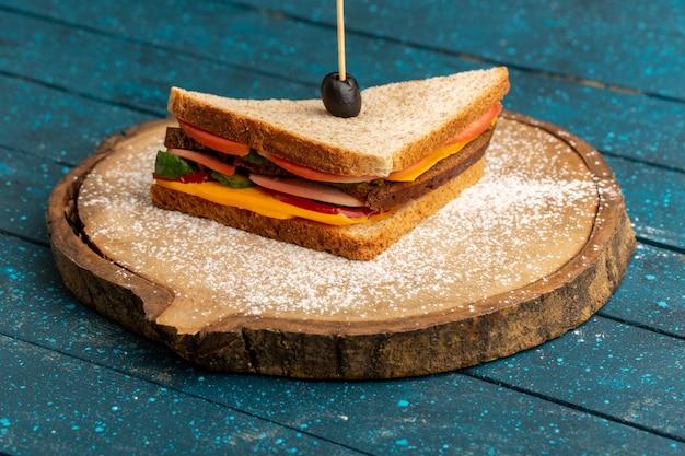 Vorderansicht leckeres toastsandwich mit käseschinken innen auf blauem holz