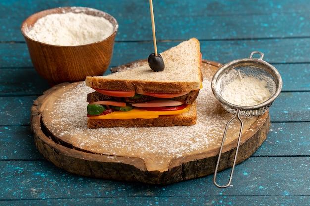 Vorderansicht leckeres toastsandwich mit käseschinken innen zusammen mit mehl auf blau