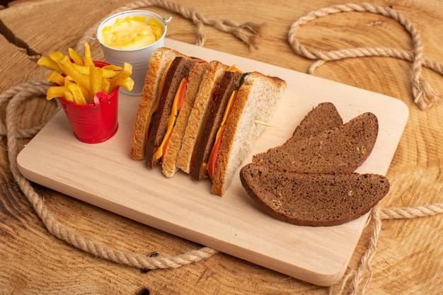 Vorderansicht leckeres toastsandwich mit käseschinken zusammen mit pommes frites sauerrahm brotlaib auf holz