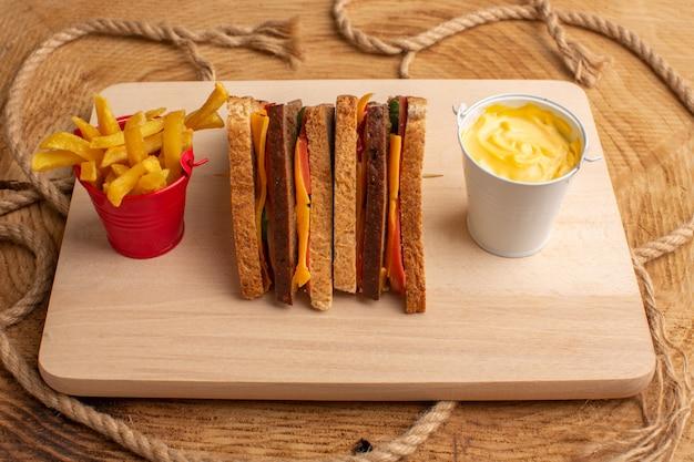 Vorderansicht leckeres toastsandwich mit käseschinken zusammen mit pommes frites saurer sahne auf holz