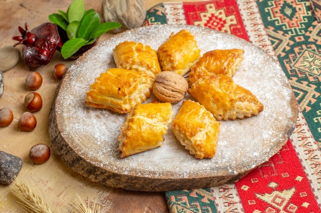 Vorderansicht leckeres walnussgebäck für tee auf braunem tischkuchenkuchen süßes gebäck