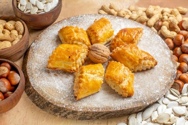 Vorderansicht leckeres walnussgebäck mit nüssen auf leichtem tischkuchenkuchen süßes gebäck