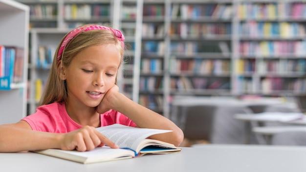 Vorderansicht mädchen, das ihre hausaufgaben in der bibliothek mit kopienraum macht