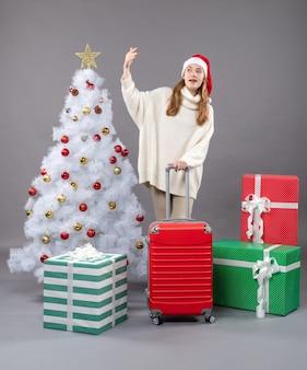 Vorderansicht mädchen, das valise hält, der weihnachtsmannhut trägt, der jemanden anruft