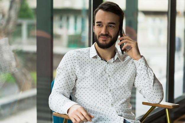 Vorderansicht männlich, der über telefon spricht