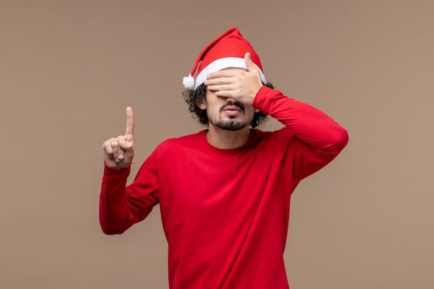 Vorderansicht männlich in rot, die seine augen auf braunem hintergrundfeiertagsemotionsweihnachten bedeckt