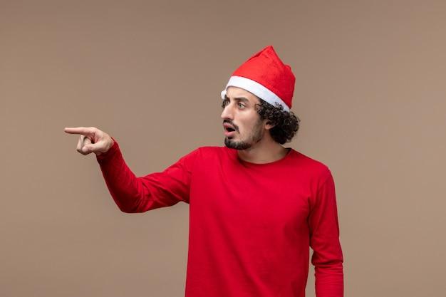 Vorderansicht männlich in rot mit verwirrtem ausdruck auf braunem hintergrundfeiertagsemotionsweihnachten