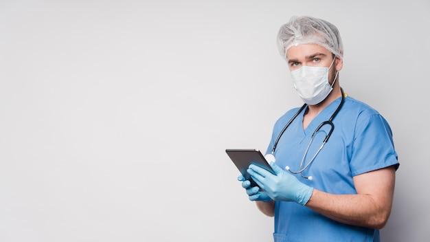 Vorderansicht männliche krankenschwester, die tablette mit kopienraum hält