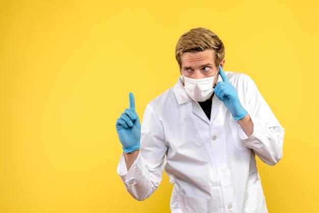 Vorderansicht männlicher arzt auf gelbem hintergrund gesundheit covid-medic