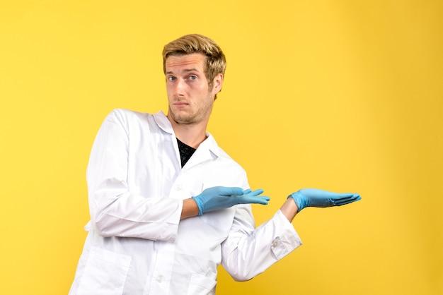 Vorderansicht männlicher arzt auf gelbem hintergrund human medic covid