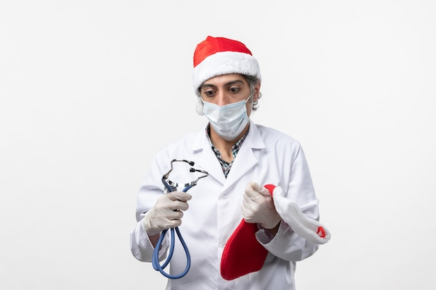 Vorderansicht männlicher arzt, der feiertagssocke auf weißwandvirus-covid-feiertagsgesundheit hält
