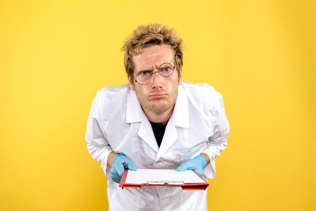 Vorderansicht männlicher arzt, der notizen auf gelbem hintergrundmedizingesundheitsmensch liest