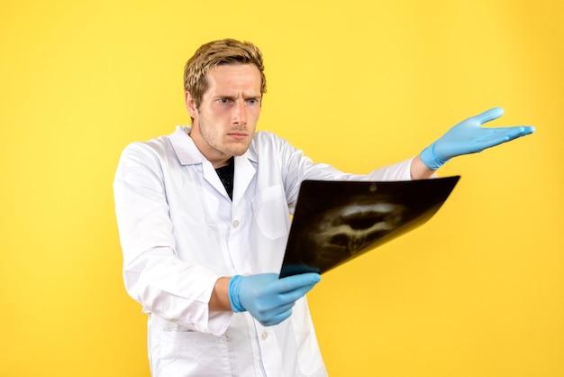 Vorderansicht männlicher arzt, der schädelröntgen auf hellgelbem hintergrundmedizinerchirurgie covid- prüft