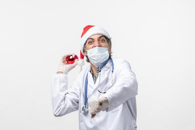Vorderansicht männlicher arzt, der wütend spielzeug auf weißwand-gesundheitsfeiertags-covid-virus wirft