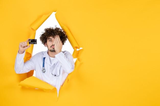 Vorderansicht männlicher arzt im medizinischen anzug, der bankkarte auf gelbem farbmedizinkrankenhauskrankheitsvirusarzt hält
