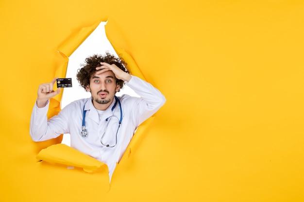 Vorderansicht männlicher arzt im medizinischen anzug, der bankkarte auf gelben zerrissenen farben hält medizinische gesundheitsmedizin virus krankenhauskrankheit