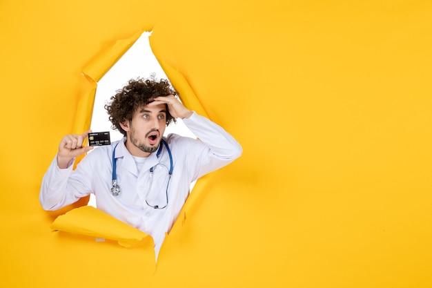 Vorderansicht männlicher arzt im medizinischen anzug, der eine bankkarte auf einer gelben zerrissenen farbe hält