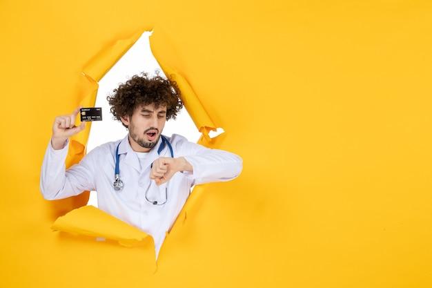 Vorderansicht männlicher arzt im medizinischen anzug, der eine bankkarte auf gelb zerrissener farbe hält