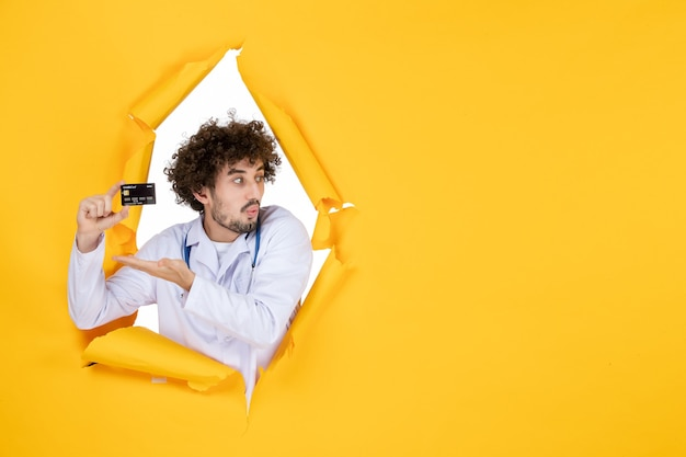 Vorderansicht männlicher arzt im medizinischen anzug, der eine bankkarte auf gelber zerrissener farbe hält