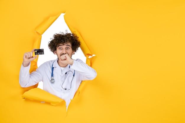 Vorderansicht männlicher arzt im medizinischen anzug, der eine bankkarte auf gelber, zerrissener farbe hält