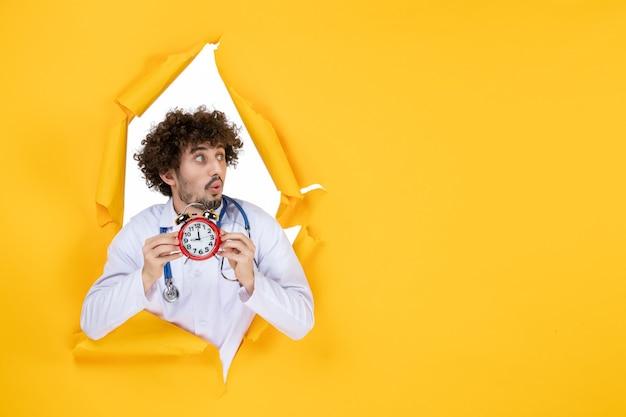 Vorderansicht männlicher arzt im medizinischen anzug, der uhren auf der gelben gesundheitsfarbe hält