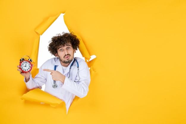 Vorderansicht männlicher arzt im medizinischen anzug, der uhren auf der gelben krankenhauseinkaufsmedizinfarbe hält