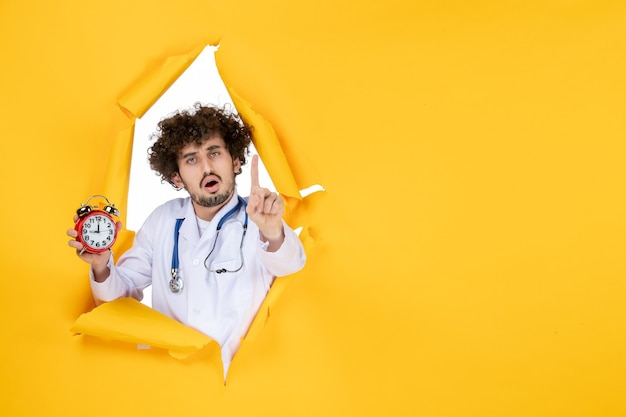 Vorderansicht männlicher arzt im medizinischen anzug, der uhren auf gelbem krankenhaus-shopping-medizin-farbzeit-gesundheit hält